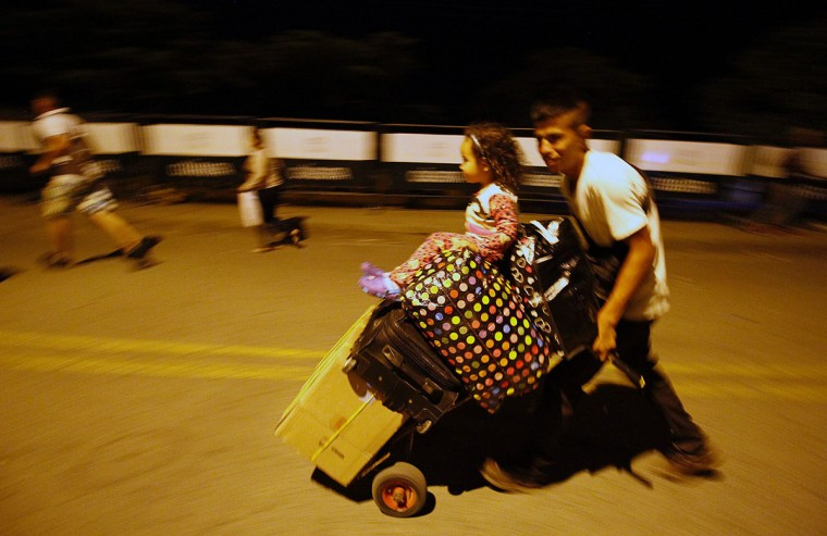 """A man walks hurriedly carrying suitcases on the Simon Bolivar bridge on the Colombian border with Venezuela, on December 12, 2016. V enezuelan President Nicolas Maduro on Monday ordered the border with Colombia sealed for 72 hours, accusing US-backed """"mafias"""" of conspiring to destabilize his country's economy by hoarding bank notes. The closure came a day after Maduro signed an emergency decree removing Venezuela's largest bank note, the 100 bolivar bill, from circulation because of what he called a Washington-sponsored plot against his country's troubled economy. (AFP PHOTO / SCHNEYDER MENDOZA)"""