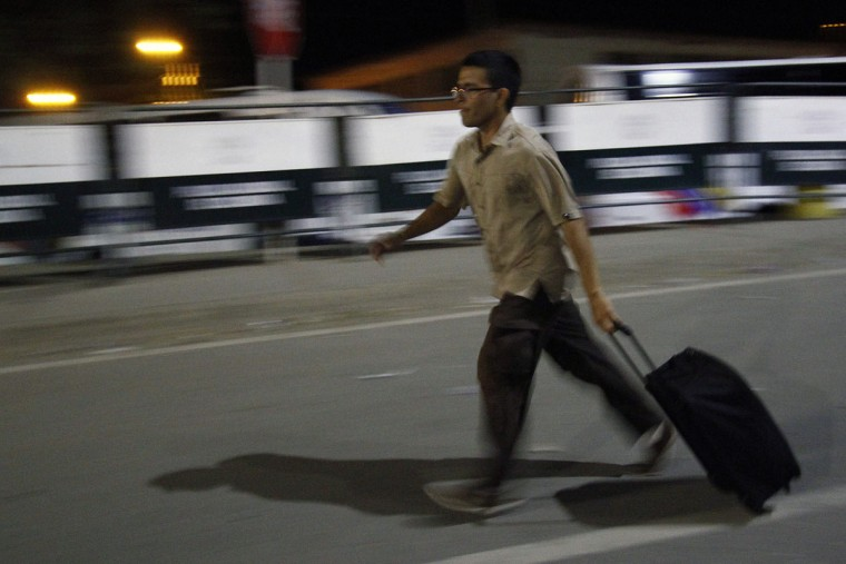 """A man walks hurriedly carrying a suitcase on the Simon Bolivar bridge on the Colombian border with Venezuela, on December 12, 2016. V enezuelan President Nicolas Maduro on Monday ordered the border with Colombia sealed for 72 hours, accusing US-backed """"mafias"""" of conspiring to destabilize his country's economy by hoarding bank notes. The closure came a day after Maduro signed an emergency decree removing Venezuela's largest bank note, the 100 bolivar bill, from circulation because of what he called a Washington-sponsored plot against his country's troubled economy. (AFP PHOTO / SCHNEYDER MENDOZA)"""