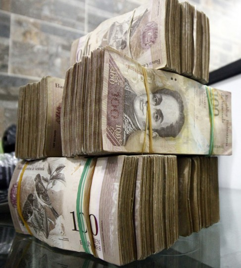 "View of 100-bolivar-bills at a bureau de change in La Parada, municipality of Villa del Rosario, Norte de Santander department, Colombia, in the border with Venezuela, on December 11, 2016. Venezuelan President Nicolas Maduro on Sunday signed an emergency decree ordering the country's largest banknote, the 100 bolivar bill, taken out of circulation to thwart ""mafias"" he accused of hoarding cash in Colombia. (AFP PHOTO / SCHNEYDER MENDOZA)"