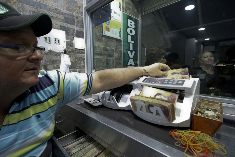 """A man counts 100-bolivar-bills on a machine at a bureau de change in La Parada, municipality of Villa del Rosario, Norte de Santander department, Colombia, in the border with Venezuela, on December 11, 2016. Venezuelan President Nicolas Maduro on Sunday signed an emergency decree ordering the country's largest banknote, the 100 bolivar bill, taken out of circulation to thwart """"mafias"""" he accused of hoarding cash in Colombia. (AFP PHOTO / SCHNEYDER MENDOZA)"""