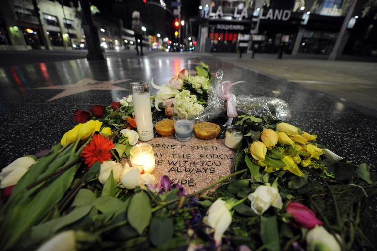 Candles and flowers are placed on actress Carrie Fisher's makeshift star on The Hollywood Walk of Fame on December, 29 2016, in Hollywood, California. (Photo by Kevork Djansezian/Getty Images)