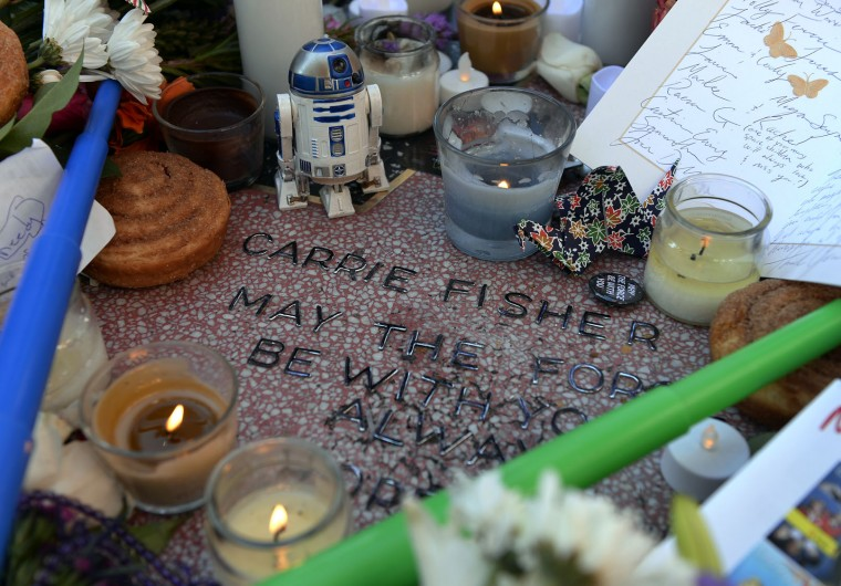 """Carrie Fisher is remembered with a makeshift star on the Hollywood Walk of Fame December 29, 2016 in Hollywood, California. The star was reportedly made by a fan who added Fisher's name to a blank star along with the words """"may the force be with you always"""" and """"hope."""" Fisher was never nominated for a star while living and now won't be eligible until the fifth anniversary of her death. (Photo by Kevork Djansezian/Getty Images)"""