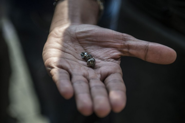 An Egyptian man shows small pieces of metal outside the Saint Peter and Saint Paul Coptic Orthodox Church after it was targeted by a bomb explosion on December 11, 2016, in Cairo's Abbasiya neighbourhood. The blast killed at least 25 worshippers during Sunday mass inside the Cairo church near the seat of the Coptic pope who heads Egypt's Christian minority, state media said. (AFP PHOTO / KHALED DESOUKI)