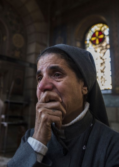 A nun reacts as Egyptian security forces (unseen) inspect the scene of a bomb explosion at the Saint Peter and Saint Paul Coptic Orthodox Church on December 11, 2016, in Cairo's Abbasiya neighbourhood. The blast killed at least 25 worshippers during Sunday mass inside the Cairo church near the seat of the Coptic pope who heads Egypt's Christian minority, state media said. (AFP PHOTO / KHALED DESOUKI)