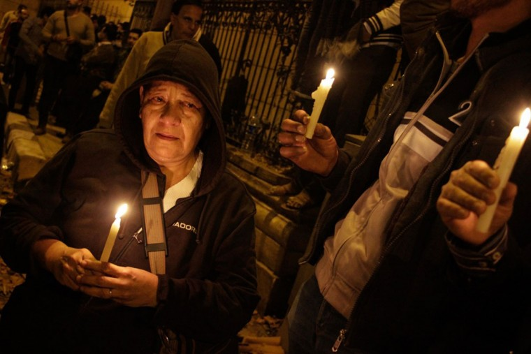 Egyptians carry candles during a vigil for the victims of a bomb explosion that targeted the Saint Peter and Saint Paul Coptic Orthodox Church on December 11, 2016, outside the Church in Cairo's Abbasiya neighbourhood. The blast killed at least 25 worshippers during Sunday mass inside the Cairo church near the seat of the Coptic pope who heads Egypt's Christian minority, state media said. (AFP PHOTO / SUHAIL SALEH)