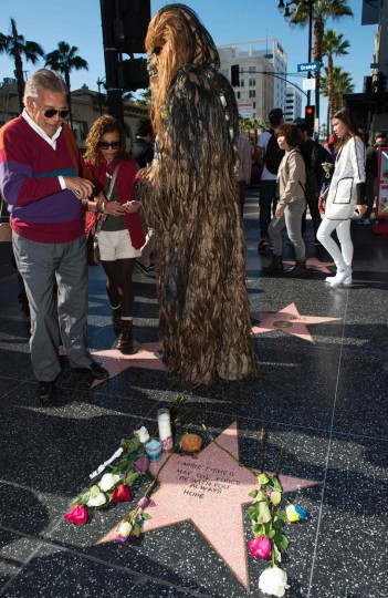 """People stop by to view a temporary star made by fans in tribute to actress Carrie Fisher on Hollywood Walk of Fame in Hollywood, California, on December 28, 2016. Friends, fans and Hollywood stars added their voices to a torrent of tributes for """"Star Wars"""" actress Carrie Fisher, who died Tuesday at the age of 60 following a heart attack. (Valerie Macon/AFP/Getty Images)"""