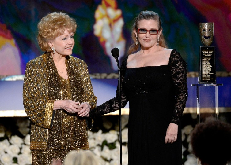 FILE - Actress Debbie Reynolds (L) accepts the Life Achievement Award from actress Carrie Fisher onstage at the 21st Annual Screen Actors Guild Awards at The Shrine Auditorium on January 25, 2015 in Los Angeles, California. (Photo by Kevork Djansezian/Getty Images)