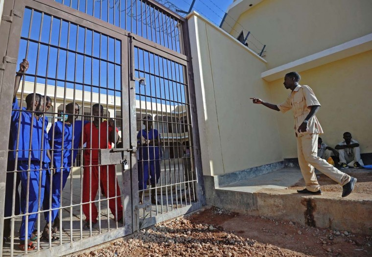 A prison warden talks to prisoners who stand behind a gate of a prison in Garowe, Puntland state, in northeastern Somalia, on December 14, 2016. The prison facilitates the rehabilitation of convicted Somali pirates and suspected Al-Shabaab jihadists. (MOHAMED ABDIWAHAB/AFP/Getty Images)