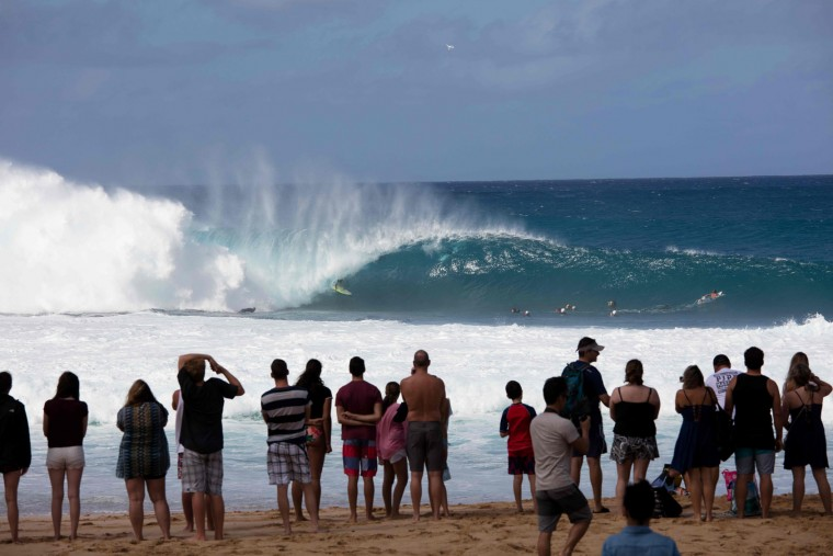 Spectators watch as Gavin Beschen of Hawaii surfs on December 25, 2016 on the island of Oahu in Hawaii, following competition in the Billabong Pipe Masters. Christmas Day at the pipeline was the best day of the winter season so far with huge tubes coming through great surfing rides and heavy wipeouts with the world's best surfers catching waves and dominating the pack. (Brian Bielmann/AFP/Getty Images)