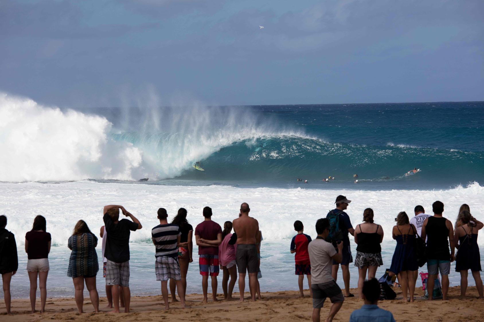 bbff9a3dc3 Spectators watch as Gavin Beschen of Hawaii surfs on December 25
