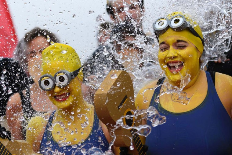 "Women disguised as Minions movie characters take part in the 78th ""Coupe de Noel"" (Christmas cup) swimming race in the Lake Geneva, on December 18, 2016 in Geneva. More than 1800 participants took part in the event, a 12-meter-long swimming off the Geneva's bank in the 7 degrees Celsius cold water. (FABRICE COFFRINI/AFP/Getty Images)"