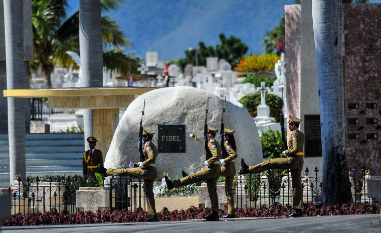 A guard of honour stays by the tomb of Cuban leader Fidel Castro at the Santa Ifigenia cemetery in Santiago de Cuba on December 4, 2016. Fidel Castro's ashes were buried alongside national heroes in the cradle of his revolution on Sunday, as Cuba opens a new era without the communist leader who ruled the island for decades. (Yamil Lage/AFP/Getty Images)
