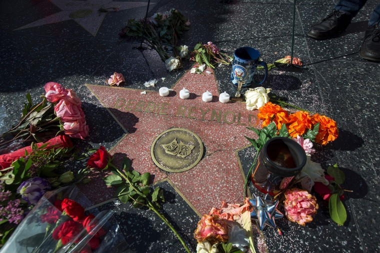 """Memorial items are left at one of the Hollywood Walk of Fame stars for actress Debbie Reynolds on December 29 in Hollywood, California. Reynolds, the """"Singin' in the Rain"""" actress who tap-danced her way into American hearts as a star of Hollywood's Golden Age, died on December 28, 2016, grief-stricken over daughter Carrie Fisher's death a day earlier. (David McNew/AFP/Getty Images)"""
