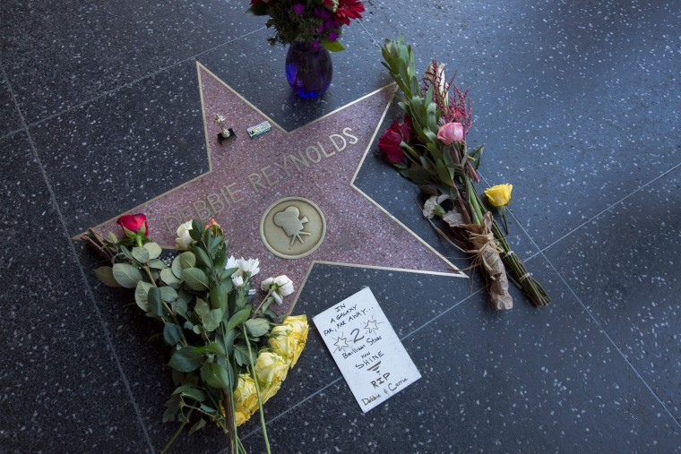 """Flowers adorn one of the Hollywood Walk of Fame stars for actress Debbie Reynolds on December 29, 2016, in Hollywood, California. Reynolds, the """"Singin' in the Rain"""" actress who tap-danced her way into American hearts as a star of Hollywood's Golden Age, died on December 28, 2016, grief-stricken over daughter Carrie Fisher's death a day earlier. (David McNew/AFP/Getty Images)"""
