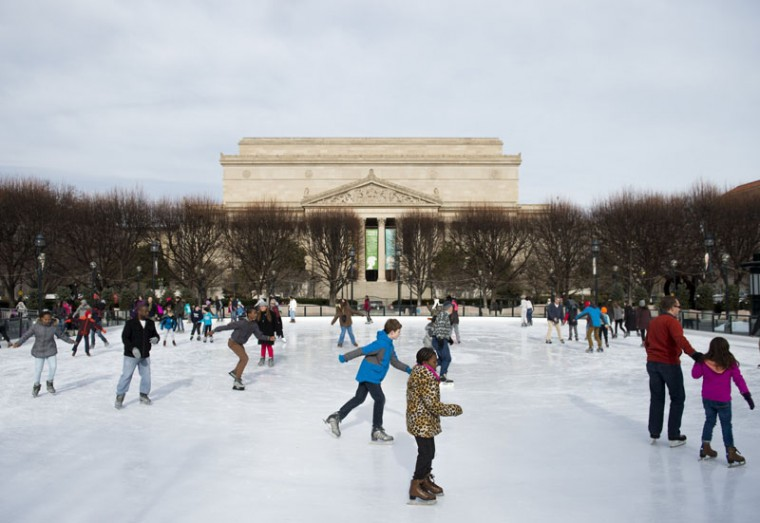 People ice skate at the National Gallery of Art's Sculpture Garden ice rink, adjacent to the National Archives in Washington, D.C., Dec. 21, 2016. (SAUL LOEB/AFP/Getty Images)