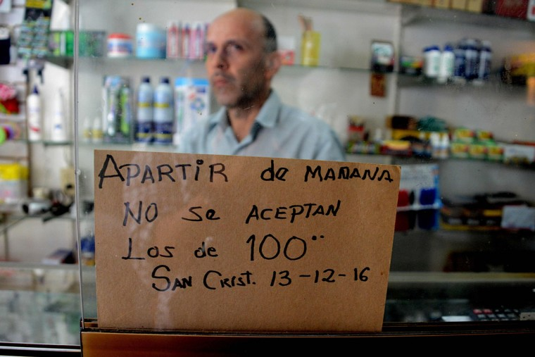 "A man is pictured behind a sign that reads: ""From tomorrow 12/13/2016 100-Bolivar-bills are not accepted"" at a shop in the border town of San Cristobal in Venezuela on December 12, 2016. Venezuelan President Nicolas Maduro on Sunday signed an emergency decree ordering the country's largest banknote, the 100 bolivar bill, taken out of circulation to thwart ""mafias"" he accused of hoarding cash in Colombia. (AFP PHOTO / GEORGE CASTELLANOS)"