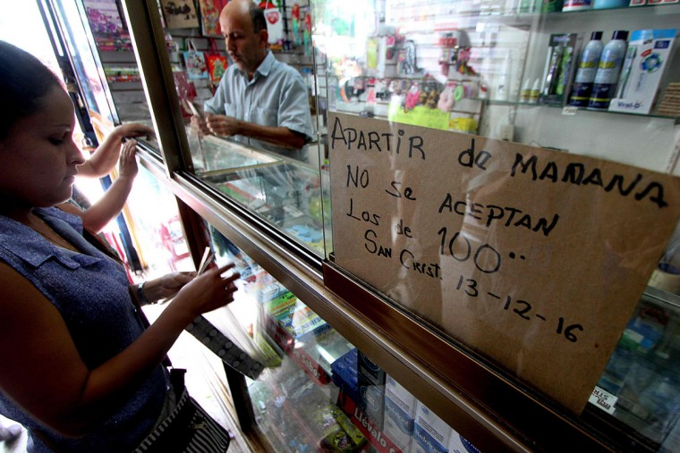 "A woman is pictured beside a sign that reads: ""From tomorrow 12/13/2016 100-Bolivar-bills are not accepted"" at a shop in the border town of San Cristobal in Venezuela on December 12, 2016. Venezuelan President Nicolas Maduro on Sunday signed an emergency decree ordering the country's largest banknote, the 100 bolivar bill, taken out of circulation to thwart ""mafias"" he accused of hoarding cash in Colombia. (AFP PHOTO / GEORGE CASTELLANOS)"
