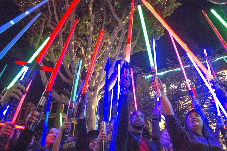 """Fans of actress Carrie Fisher honored her death by pointing their lit """"Star Wars"""" light sabers to the sky at 7 p.m. at Downtown Disney, Wednesday night, Dec. 28, 2016, in Anaheim. (Mark Eades/The Orange County Register via AP)"""