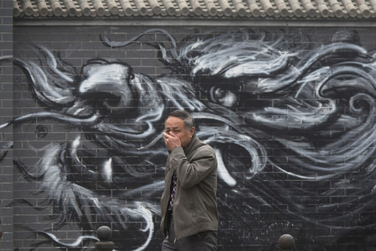 A man places his hand over his mouth as he walks past graffiti of a dragon on a street in Beijing, China, Tuesday, Dec. 20, 2016. Thick, gray smog fell over Beijing on Tuesday, choking China's capital in a haze that spurred authorities to cancel flights and close some highways in emergency measures to cut down on air pollution. (AP Photo/Ng Han Guan)