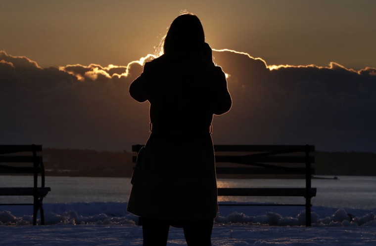 Amanda Wreggelsworth, of Portland, Maine, photographs the frigid sunrise as it highlights a bank of clouds over Casco Bay, Thursday, Dec. 15, 2016, in Portland, Maine. Much of the northern Mid-Atlantic and Northeast will stay cold for the next couple of days as the arctic air remains stuck over the northern Appalachians, the National Weather Service said. (AP Photo/Robert F. Bukaty)