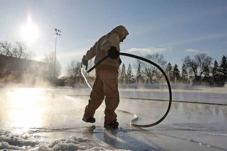Tiara Medlock, a park keeper with the Minneapolis Parks and Recreation maintenance department, sprays water to form an ice skating rink as temperatures dipped below zero, Thursday, Dec. 15, 2016 in Minneapoilis. (Anthony Souffle/Star Tribune via AP)