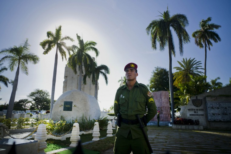 A soldier of the Revolutionary Armed Forces ( FAR ) stand in guard next to the tomb of Cuba's leader Fidel Castro at the Santa Ifigenia cemetery in Santiago, Cuba, Saturday, Dec. 3, 2016. A wooden box containing Fidel Castro's ashes was placed by his brother and successor Raul on Sunday into the side of a granite boulder that has become Cuba's only official monument to the charismatic bearded rebel. (AP Photo/Ramon Espinosa)