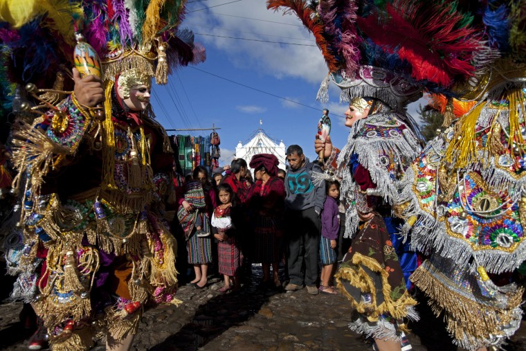 Masked dancers perform outside St. Thomas church during a celebration honoring the patron saint of Chichicastenango, Guatemala, Wednesday, Dec. 21, 2016. The church is built atop a former temple and incorporates the temple's 18 steps, each representing a month of the Mayan calendar. (AP Photo/Moises Castillo)