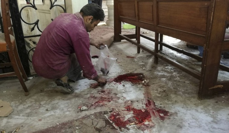 A worker cleans the scene inside St. Mark Cathedral in central Cairo, following a bombing, Sunday, Dec. 11, 2016. The blast at Egypt's main Coptic Christian cathedral killed dozens of people and wounded many others on Sunday, according to Egyptian state television, making it one of the deadliest attacks carried out against the religious minority in recent memory. (Omar El-Hady via AP)