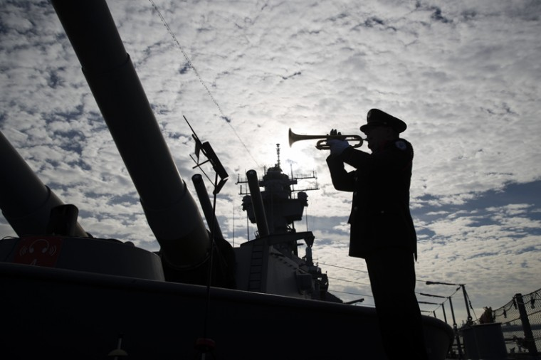 On board The Battleship New Jersey Museum and Memorial in Camden, N.J., Greg Murphy plays the Navy Hymn during a ceremony commemorating the 75th anniversary of the Dec. 7, 1941, Japanese attack on Pearl Harbor. (AP Photo/Matt Rourke)