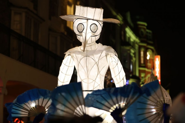 Performers dance in the street as the Burning the Clocks parade of lanterns moves through Brighton, England as part of celebrations of the Winter Solstice. (Andrew Matthews/PA via AP)