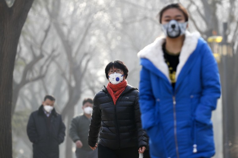 "Chinese people wearing masks for protection against pollution walk at Ritan Park shrouded by heavy smog in Beijing, Monday, Dec. 19, 2016. Chinese cities are limiting the number of cars on roads and have temporarily shut down factories to cut down pollution during a national ""red alert"" for smog. (AP Photo/Andy Wong)"