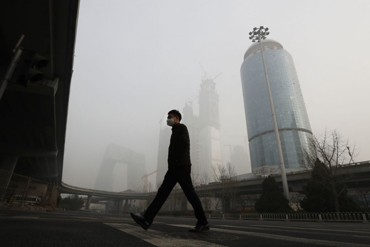 A man wearing a mask for protection against air pollution walks across a road in Beijing as the capital of China is shrouded by heavy smog on Tuesday, Dec. 20, 2016. Thick, gray smog fell over Beijing on Tuesday, clouding China's capital in a haze that spurred authorities to cancel flights and close some highways in emergency measures to cut down on air pollution. (AP Photo/Andy Wong)