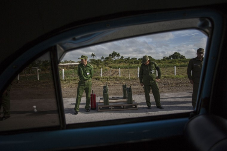 In this Dec. 2, 2016 photo, soldiers stand beside diesel tanks and a fire extinguisher to refill the vehicles of the funeral procession carrying the ashes of Cuba's late leader Fidel Castro, outside Las Tunas, Cuba. Castro's ashes journeyed across Cuba from Havana to their final resting place in the eastern city of Santiago through small towns and cities where his rebel army fought its way to power nearly 60 years ago. (AP Photo/Desmond Boylan)