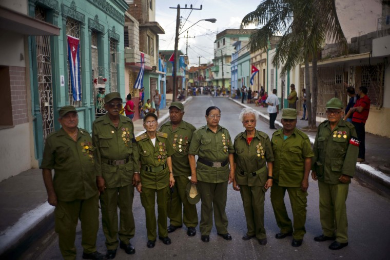 In this Dec. 2, 2016 photo, seniors who were part of Fidel Castro's rebel force during Cuba's revolution pose for a group portrait, before Castro's funeral procession passes through Bayamo, Cuba. Castro's ashes travelled in a four-day journey across Cuba through small towns and cities where his rebel army fought its way to power nearly 60 years ago, to their final resting place in the eastern city of Santiago. (AP Photo/Ramon Espinosa)