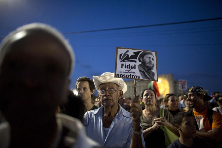 """In this Nov. 29, 2016 photo, a man holds a sign with a picture of Fidel Castro that reads in Spanish """"Fidel among us'"""" during a rally honoring the late Cuban leader at Revolution Plaza in Havana, Cuba. Schools and government offices were closed in homage to Fidel Castro, with the day ending in a rally on the wide plaza where the Cuban leader delivered fiery speeches to mammoth crowds in the years after he seized power. (AP Photo/Natacha Pisarenko)"""