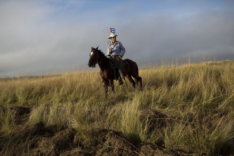 In this Dec. 2, 2016 photo, a villager mounted on his horse waits for the ashes of Cuba's late leader Fidel Castro as they drive along the central road in Las Tunas, Cuba. On the lonely roads of eastern Cuba, people waited for hours to salute the casket holding Fidel Castro's ashes. (AP Photo/Rodrigo Abd)