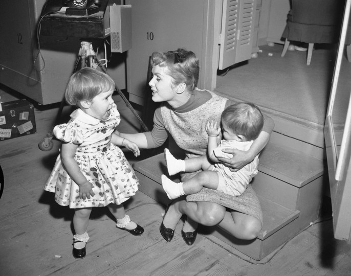 """FILE- In this Feb. 27, 1959, file photo, working long hours on the set of """"Say One For Me,"""" so she can fly to Spain and start another movie, actress Debbie Reynolds is visited at the studio by her children, Carrie, 2, and 1-year-old Todd. Reynolds, star of the 1952 classic """"Singin' in the Rain"""" died Wednesday, Dec. 28, 2016, according to her son Todd Fisher. She was 84. (AP Photo, File)"""
