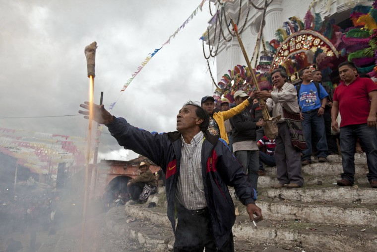 A man launches a firecracker during a celebration honoring Saint Thomas, the patron saint of Chichicastenango, Guatemala, Wednesday, Dec. 21, 2016. After eight uninterrupted days of celebration in honor of the patron Saint Thomas in the Mayan town, fireworks accompany three bands that play simultaneously at the corners of the most emblematic market in Guatemala. (AP Photo/Moises Castillo)