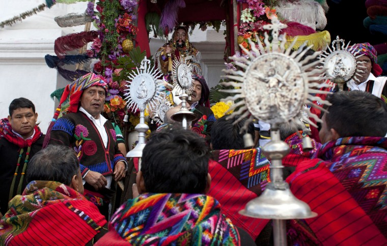 Members of a brotherhood pray after a procession in honor of Saint Thomas, the patron saint of Chichicastenango, Guatemala, Wednesday, Dec. 21, 2016. K'iche' Mayans make up 14 Catholic brotherhoods that parade through the mountain town behind Saint Thomas. (AP Photo/Moises Castillo)
