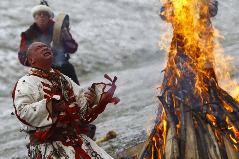 Hungarian Artist Miklos Zoltan Baji performs a shamanic ritual around a bonfire during winter solstice celebrations on Wednesday, Dec. 21, 2016, in Bekescsaba, about 125 miles southeast of Budapest, Hungary. (Peter Lehoczky/MTI via AP)