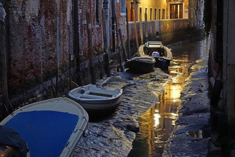 Boats sit on the muddy sea bed of the Venetian lagoon in the Rio dei Meloni area, in Venice, Thursday, Dec. 29, 2016. An uncommon low tide hampered boat circulation in many areas of the city that is built on an archipelago where canals serve the function of roads. (Andrea Merola/ANSA via AP)