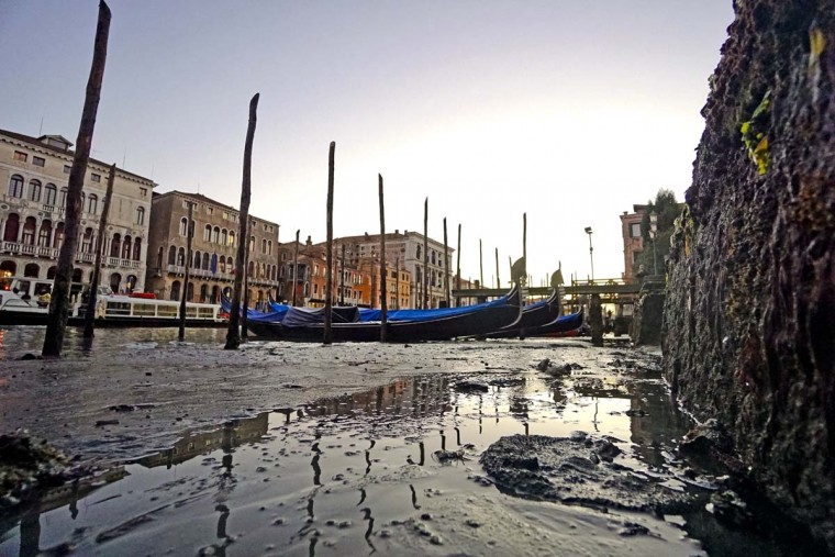 Gondolas sit on the muddy sea bed of the Venetian lagoon in the Riva del Vin area, in Venice, Thursday, Dec. 29, 2016. An uncommon low tide hampered boat circulation in many areas of the city that is built on an archipelago where canals serve the function of roads. (Andrea Merola/ANSA via AP)