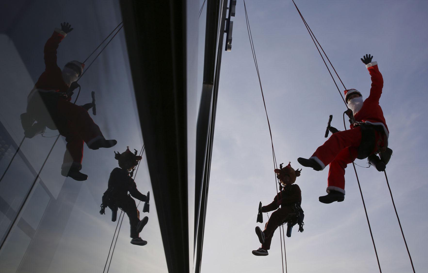 Santa Clauses clean windows in Japan
