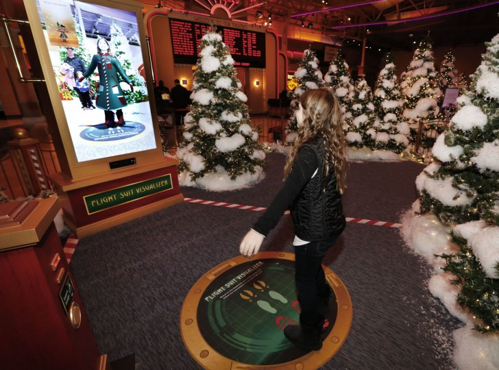 In this Monday, Nov. 21, 2016, photo, Natalia Santia, 9, tries the flight suit visualizer at Santa's Flight Academy in Great Lakes Crossing Outlets in Auburn Hills, Mich. In an effort to lure online shoppers to their stores, many malls are upgrading the traditional visit to Santa into a high-tech experience. (AP Photo/Paul Sancya)