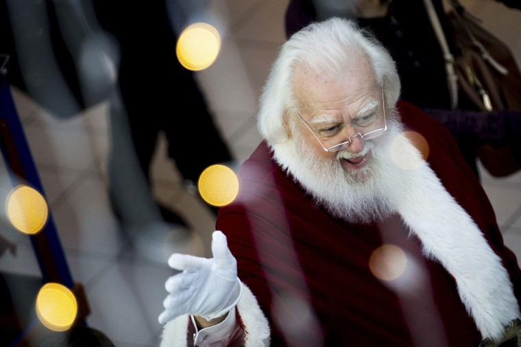 "In this Sunday, Nov. 20, 2016, photo, Santa Claus waves to mall shoppers as he makes his way to the ""Adventure to Santa,"" a DreamWorks DreamPlace experience at North Point Mall, in Alpharetta, Ga. The Santa experience has gotten a makeover as many malls install shows and games they hope will lure shoppers who are buying more online. (AP Photo/Branden Camp)"