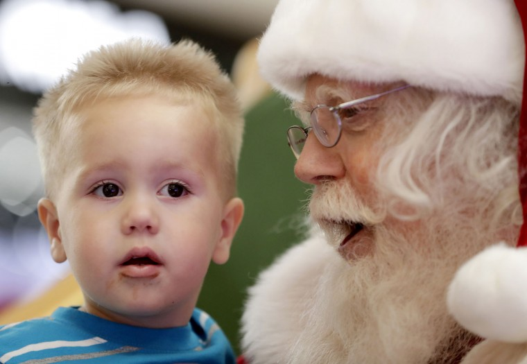 In this Thursday, Nov. 17, 2016, photo, Landen Brunn, 2, has his photo taken with Santa Roger Edmonds at the Santa HQ at the Chandler Mall, in Chandler, Ariz. In an effort to lure online shoppers to their stores, many malls are upgrading the traditional visit to Santa into a high-tech spectacle. (AP Photo/Matt York)