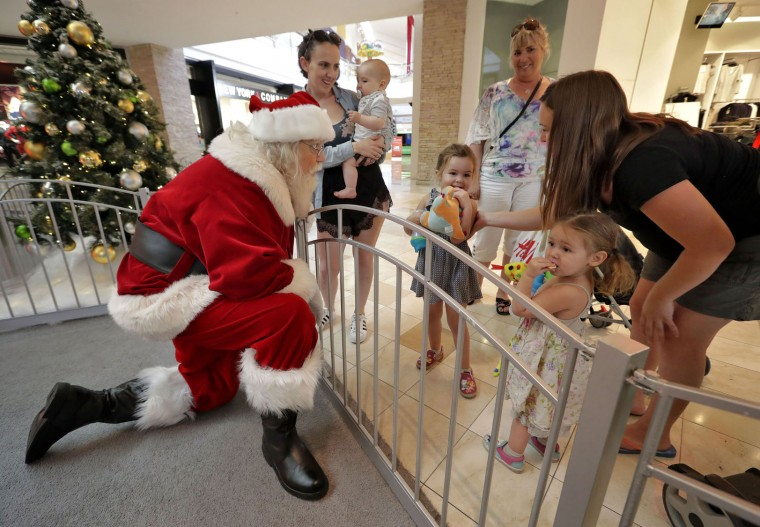 In this Thursday, Nov. 17, 2016, photo, Santa Roger Edmonds talks with kids at the Santa HQ at the Chandler Mall, in Chandler, Ariz. In an effort to lure online shoppers to their stores, many malls are upgrading the traditional visit to Santa into a high-tech spectacle. (AP Photo/Matt York)