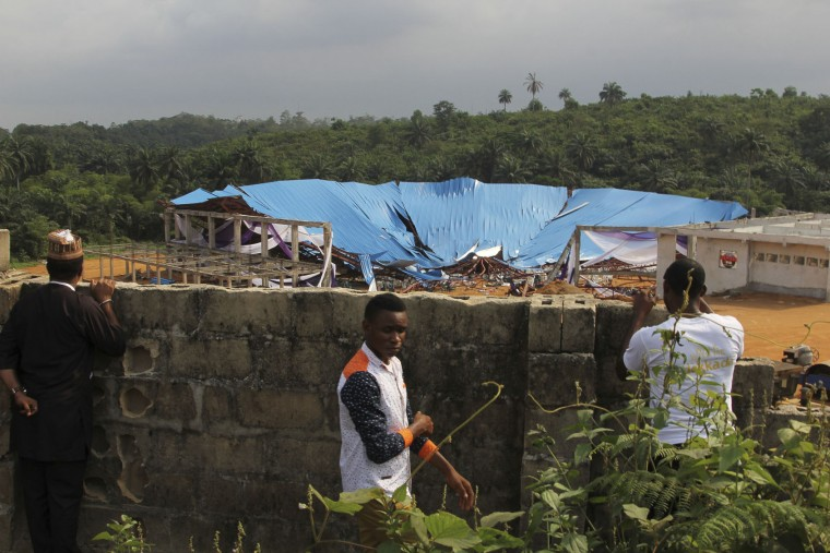 People gathered at the site of a collapsed church in Uyo, Nigeria, Sunday, Dec. 11, 2016. Metal girders and the roof of a crowded church collapsed onto worshipers in southern Nigeria, Saturday, killing at least 160 people with the toll likely to rise, a hospital director said Sunday. (AP Photo)