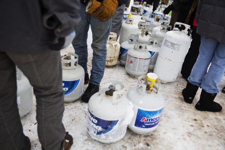 People wait to have their propane tanks filled at the Oceti Sakowin camp where people have gathered to protest the Dakota Access oil pipeline in Cannon Ball, N.D., Thursday, Dec. 1, 2016. (AP Photo/David Goldman)
