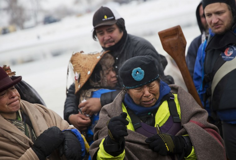 In this Thursday, Dec. 1, 2016 photo, Patty Sam Porter of Colville, Wash., right, cries after reaching shore by canoe with fellow members of the Colville Native American tribe, J.P. Pacodas, left, and Virginia Redstar, rear, at the Oceti Sakowin camp where people have gathered to protest the Dakota Access oil pipeline in Cannon Ball, N.D. The women traveled from Montana with fellow tribal members on canoe for 10 days down the Missouri river to reach the camp. (AP Photo/David Goldman)